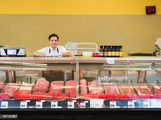 Hispanic butcher at meat counter of grocery store