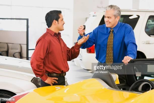 Hispanic car salesman handing car keys to buyer