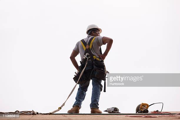 hispanic carpenter standing on the roofing with a hammer, circular saw and a nail gun - safety harness stock photos and pictures