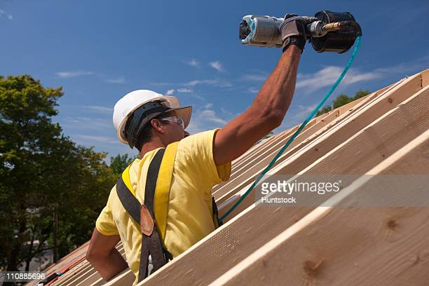 Hispanic carpenter using nail gun on roofing at a house under construction