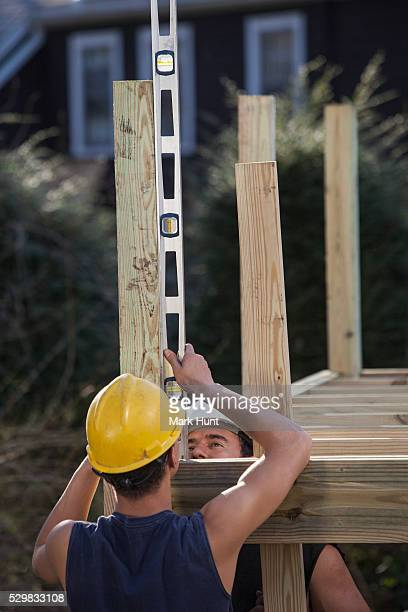 Hispanic carpenters using a level on deck post construction
