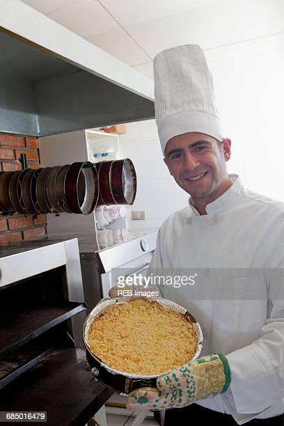 Hispanic chef holding cheesecake near oven
