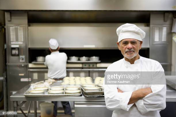 Hispanic chef in uniform in commercial kitchen