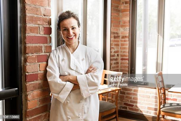 Hispanic chef leaning against wall in cafe