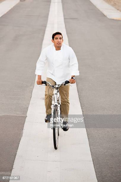 Hispanic chef riding bicycle on line in street