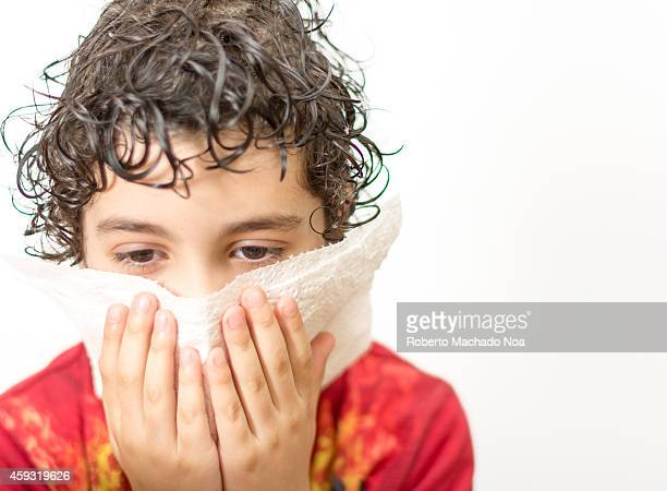 Hispanic child boy blowing his nose while suffering from a cold or flu virus