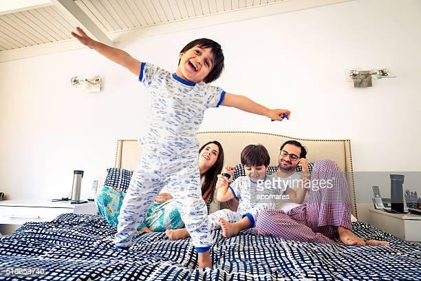 Hispana niños cuadrados con cama de cerrar con padres