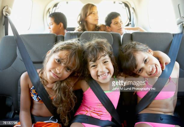 hispanic children in car wearing seatbelts - medium group of people stock pictures, royalty-free photos & images