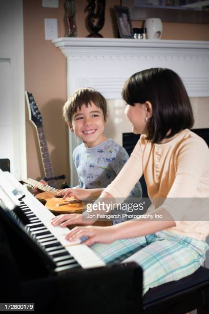 hispanic children playing music in living room - germantown maryland stock photos and pictures