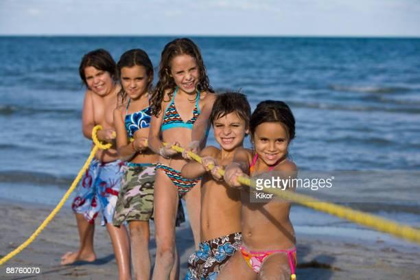Hispanic children playing tug-of-war on beach