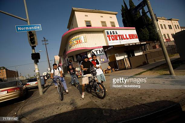 Hispanic children ride their bikes along Normandie Street and Wilshire Boulevard on August 3 2006 in Los Angeles California The area was first...