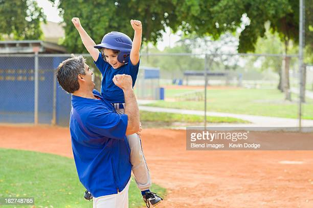 Hispanic coach and young baseball player cheering