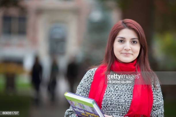 hispanic college student holding books on campus - pañuelo rojo fotografías e imágenes de stock