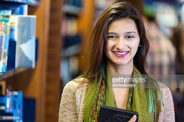 Hispanic college student smiling while studying in library