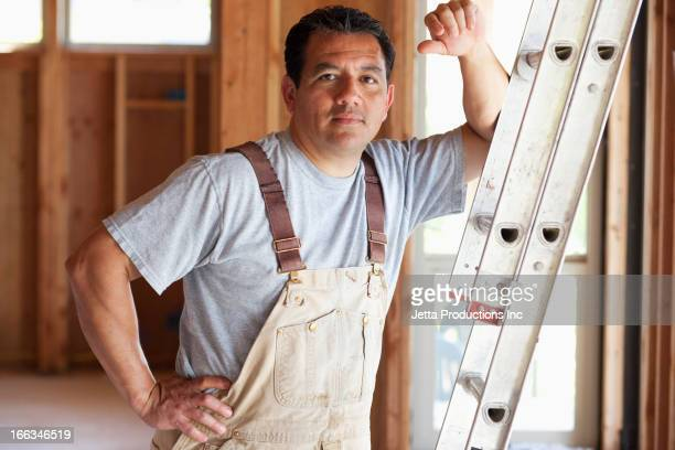 Hispanic construction worker leaning on ladder in unfinished room