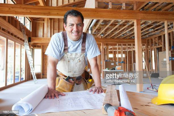 hispanic construction worker looking at blueprints in unfinished room - building contractor stock pictures, royalty-free photos & images