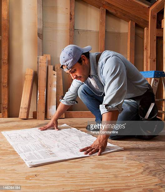Hispanic construction worker looking at blueprints
