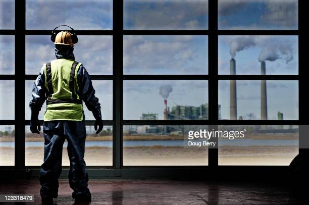 Hispanic construction worker looking out window at factory