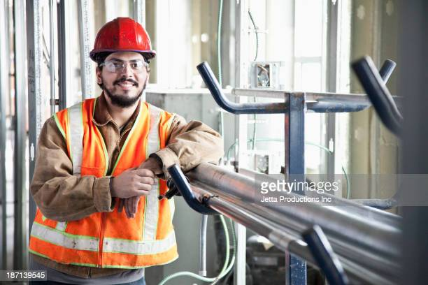 Hispanic construction worker smiling at construction site