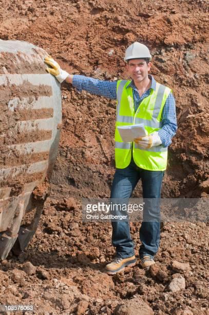 Hispanic construction worker standing in dirt