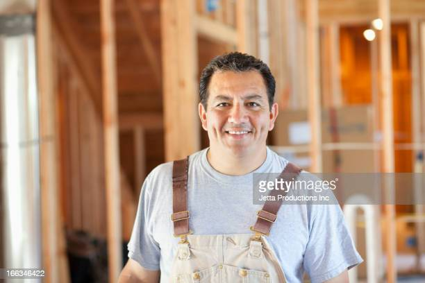 Hispanic construction worker standing in unfinished room