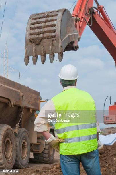 Hispanic construction worker watching backhoe