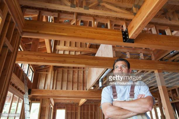 Hispanic construction worker with arms crossed in unfinished room