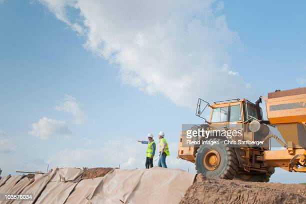 Hispanic construction workers in field with dump truck