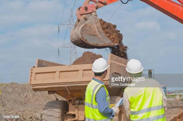 hispanic construction workers watching dirt falling into dump truck - ダンプカー ストックフォトと画像