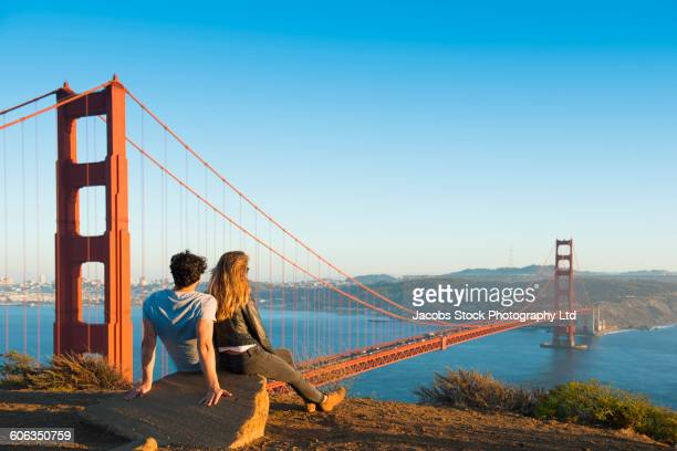 hispanic couple admiring golden gate bridge, san francisco, california, united states - san francisco california stock photos and pictures