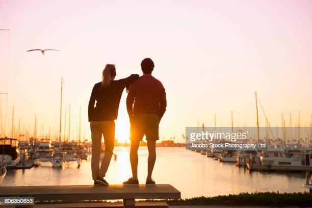 hispanic couple admiring marina - marina stock photos and pictures