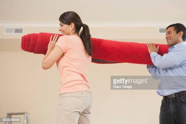 Hispanic couple carrying carpet in new home