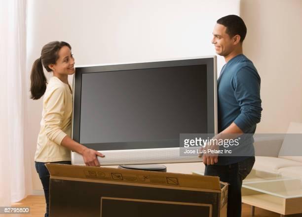 hispanic couple carrying new television - 大型テレビ ストックフォトと画像