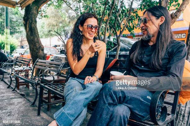 Hispanic Couple chatting with coffee outdoors