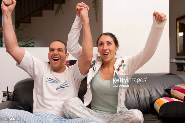 Hispanic couple cheering and watching television