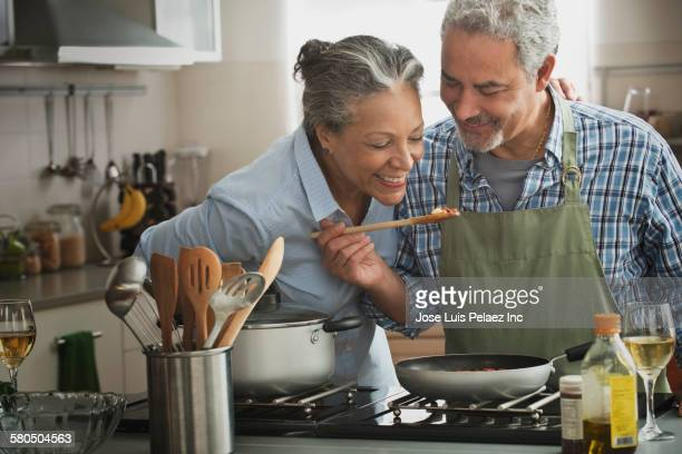 hispanic couple cooking in kitchen - cozinhando - fotografias e filmes do acervo