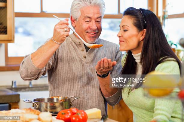 hispanic couple cooking together in kitchen - savory food stock pictures, royalty-free photos & images