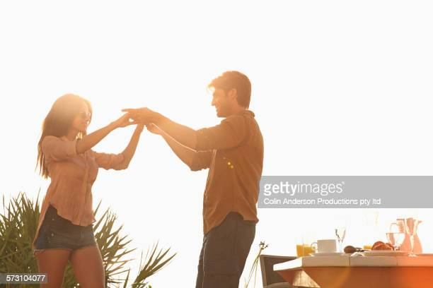 Hispanic couple dancing at table outdoors