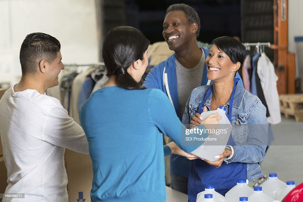 Hispanic couple donating water and blankets at disaster relief charity : Stock Photo