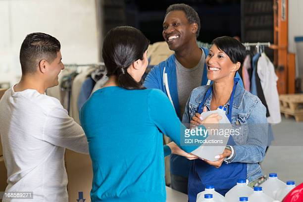 hispanic couple donating water and blankets at disaster relief charity - humanitarian aid stock pictures, royalty-free photos & images