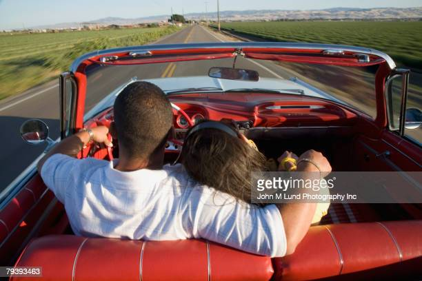 Hispanic couple driving in convertible