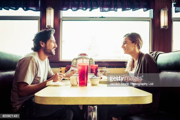 hispanic couple eating breakfast in diner - man eating woman out - fotografias e filmes do acervo