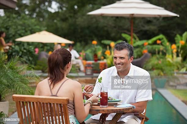 ヒスパニックのカップルのお食事、屋外プール近く