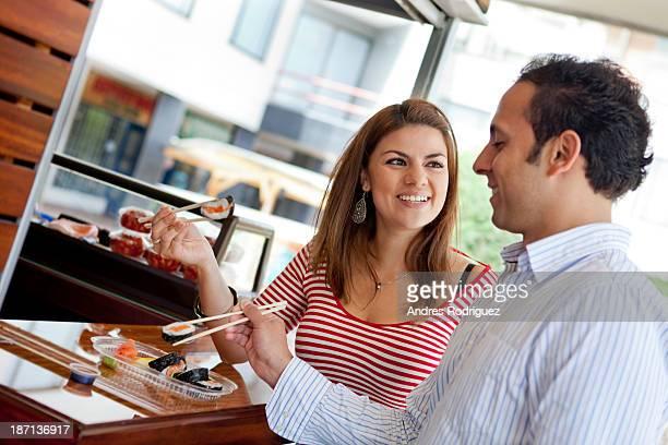 Hispanic couple eating sushi together