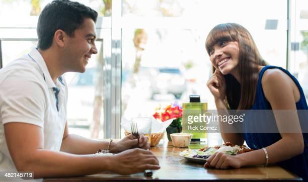 Hispanic couple eating together at cafe