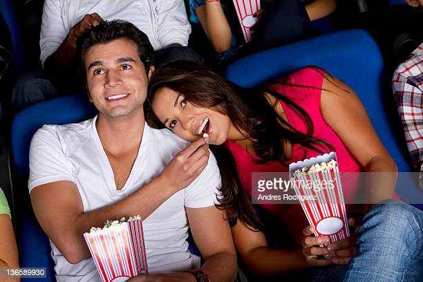 Hispanic couple enjoying popcorn at movie theater