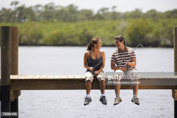 hispanic couple fishing on pier - jetty stock pictures, royalty-free photos & images