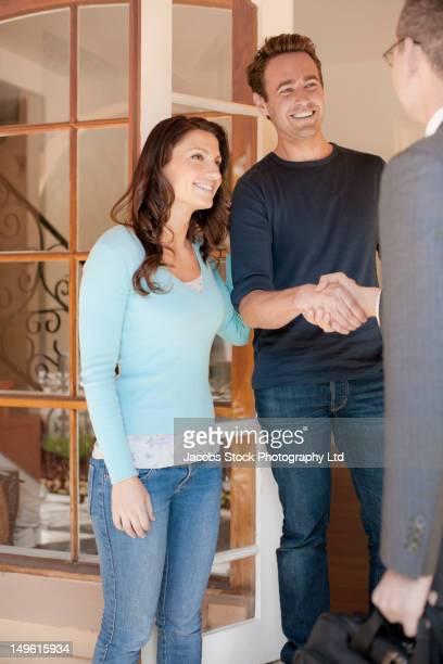 Hispanic couple greeting financial advisor