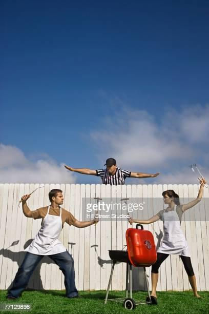 Hispanic couple having barbeque battle