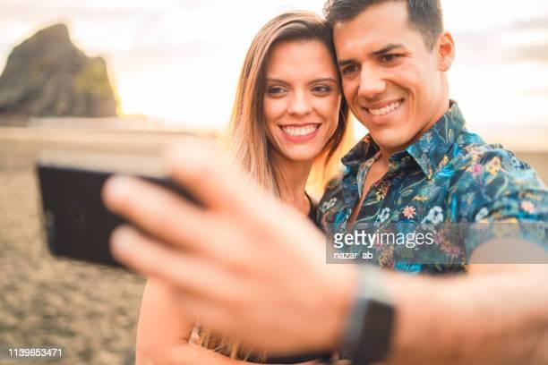 Hispanic couple having selfie together.
